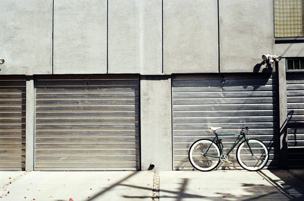 Un vélo posé devant une porte de garage